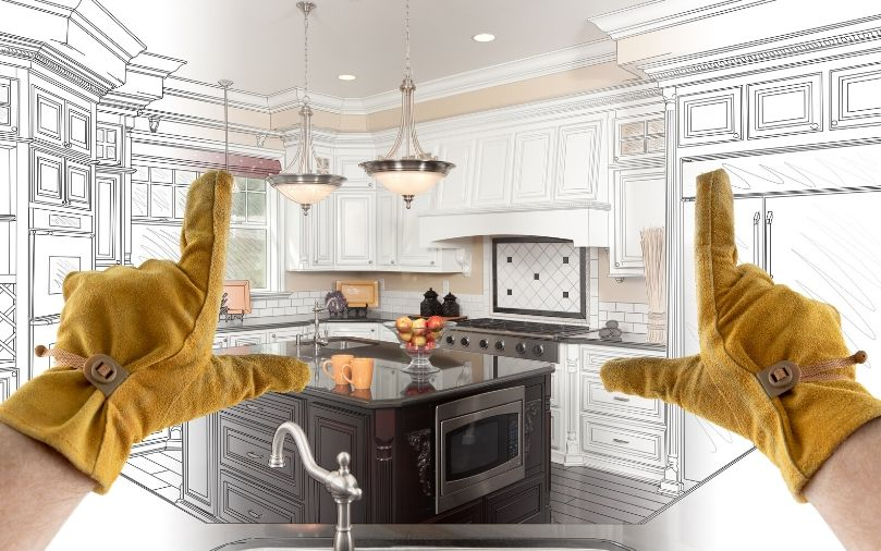 A person wearing work gloves making the 'picturing' hand gesture on a model kitchen.